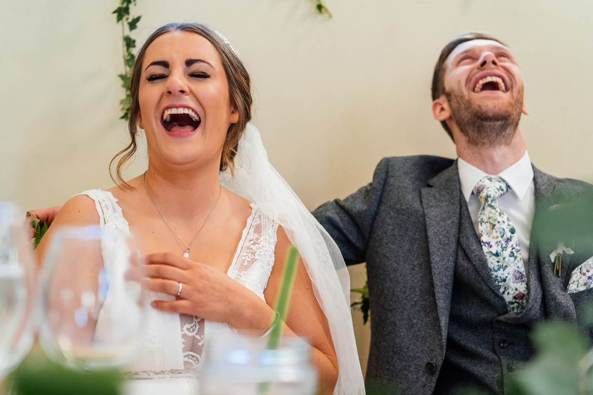bride and groom laughing at the speeches