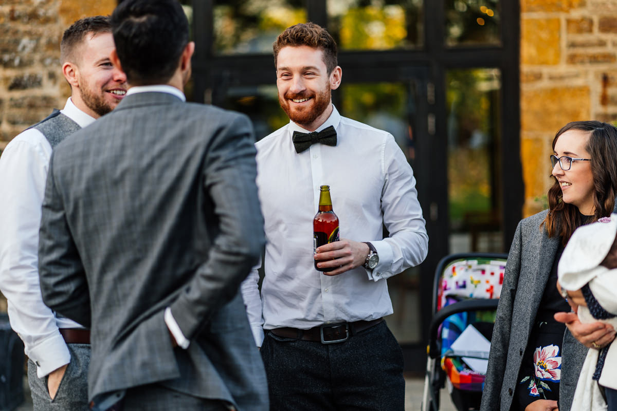 candid photo of wedding guests chatting and drinking