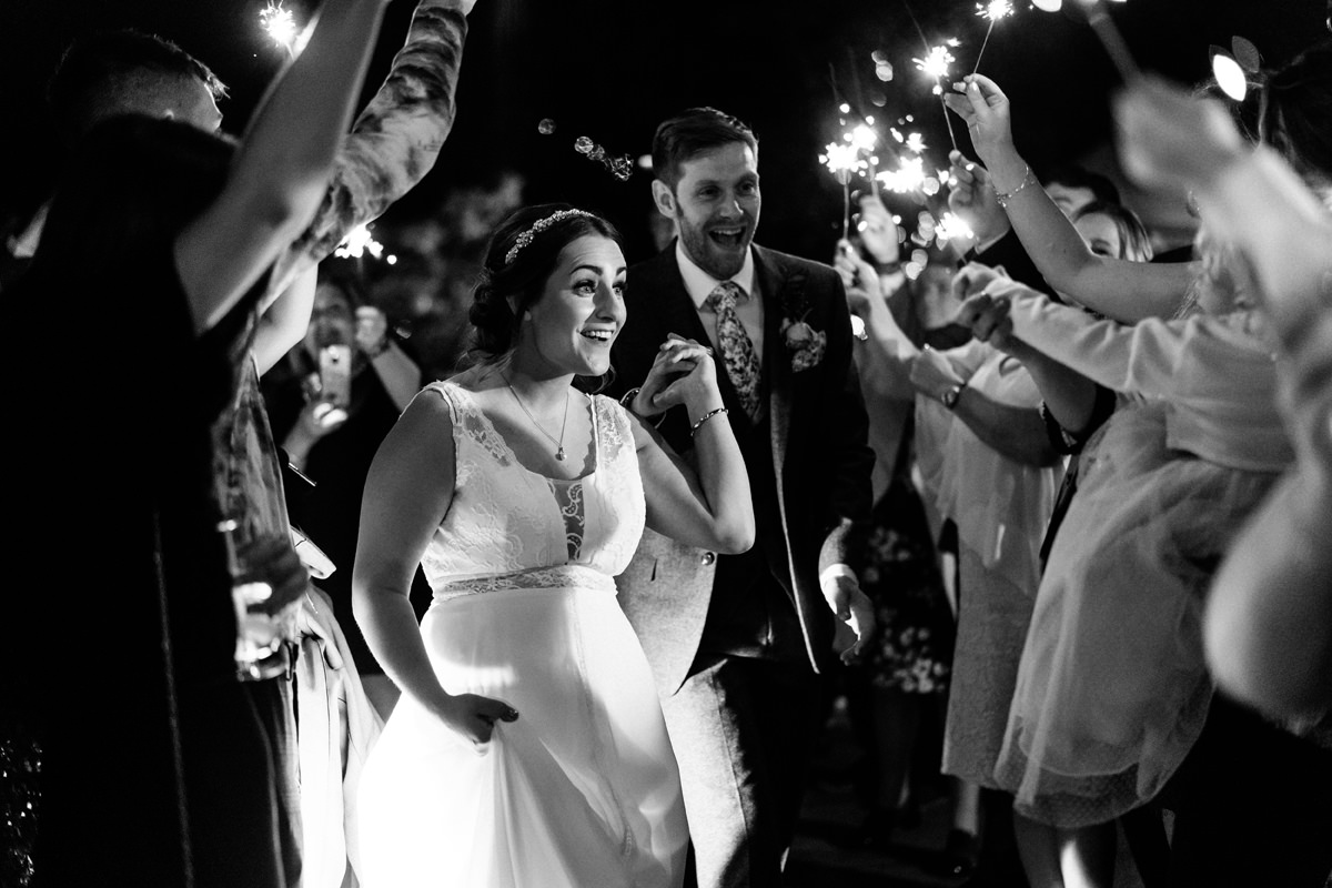 bride and groom walk through sparklers