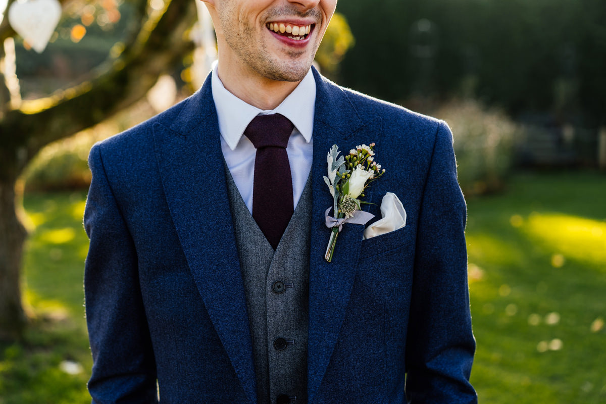 groom suit detail and button hole flower