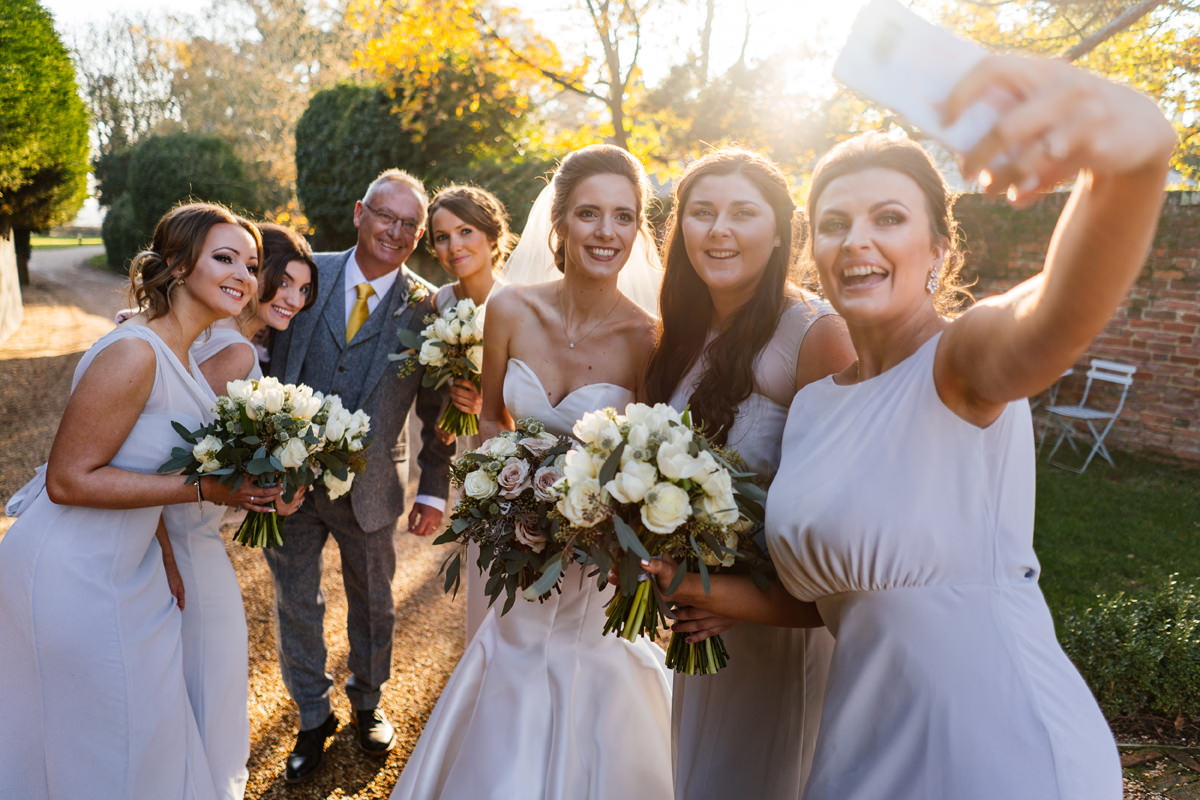 selfie with bride, bridesmaids and father of the bride