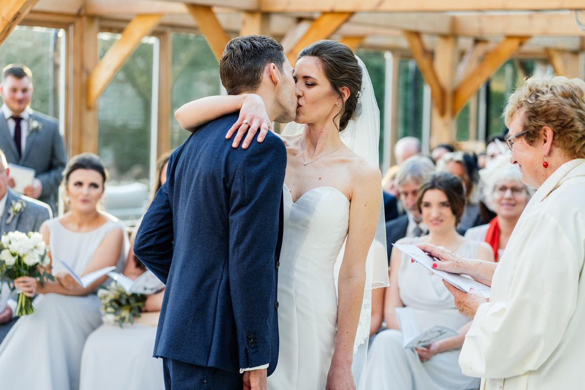 bride and groom have their first kiss