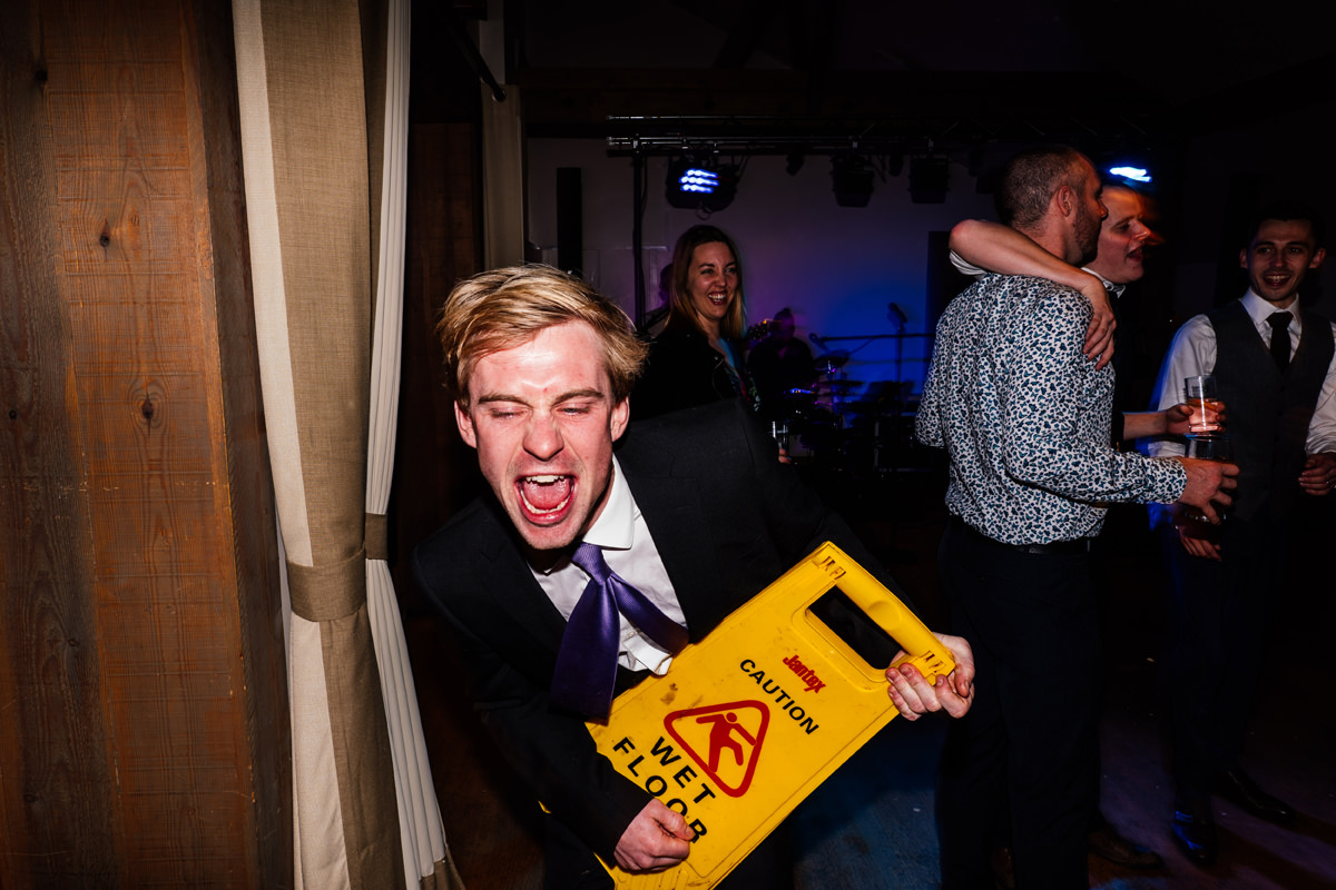 wedding guest playing air guitar with a wet floor sign