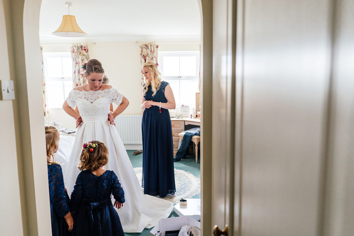 bride getting her dress on helped by her bridesmaids