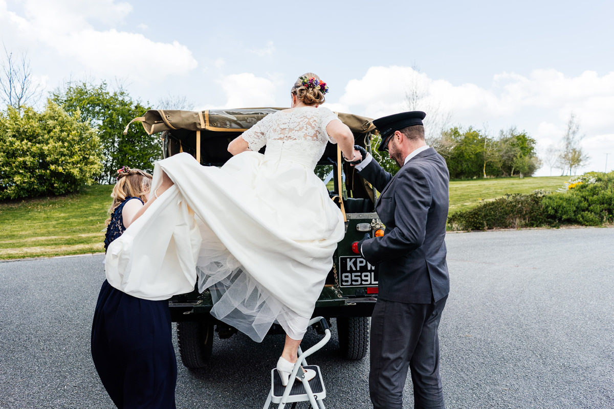 bride getting into the back of her wedding car - landcover defender