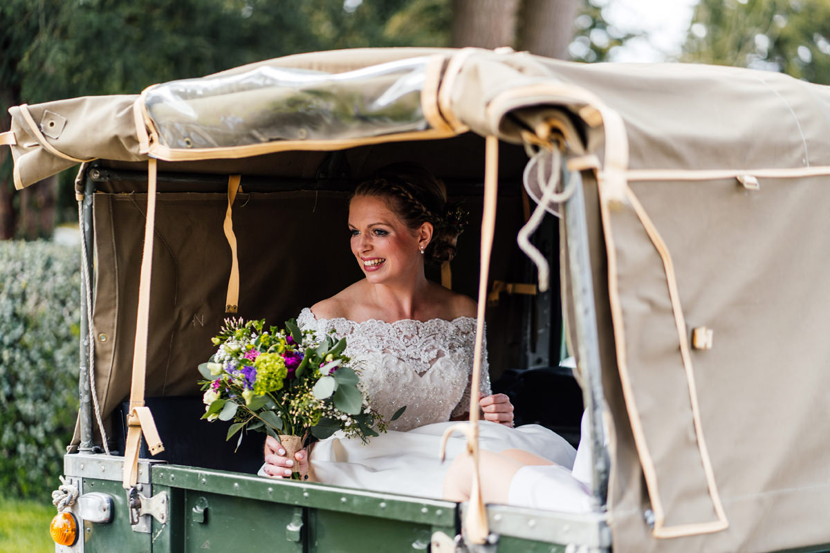 bride arriving at the church ceremony in landcover defender