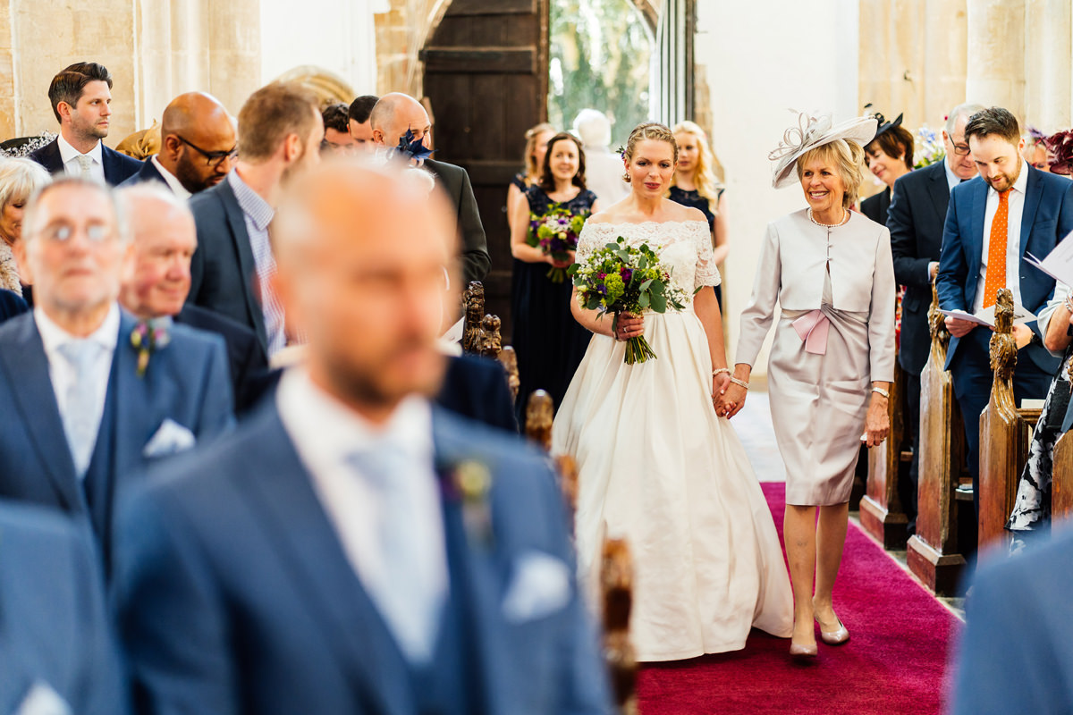 mum walks bride up the aisle in church at the beginning of ceremony