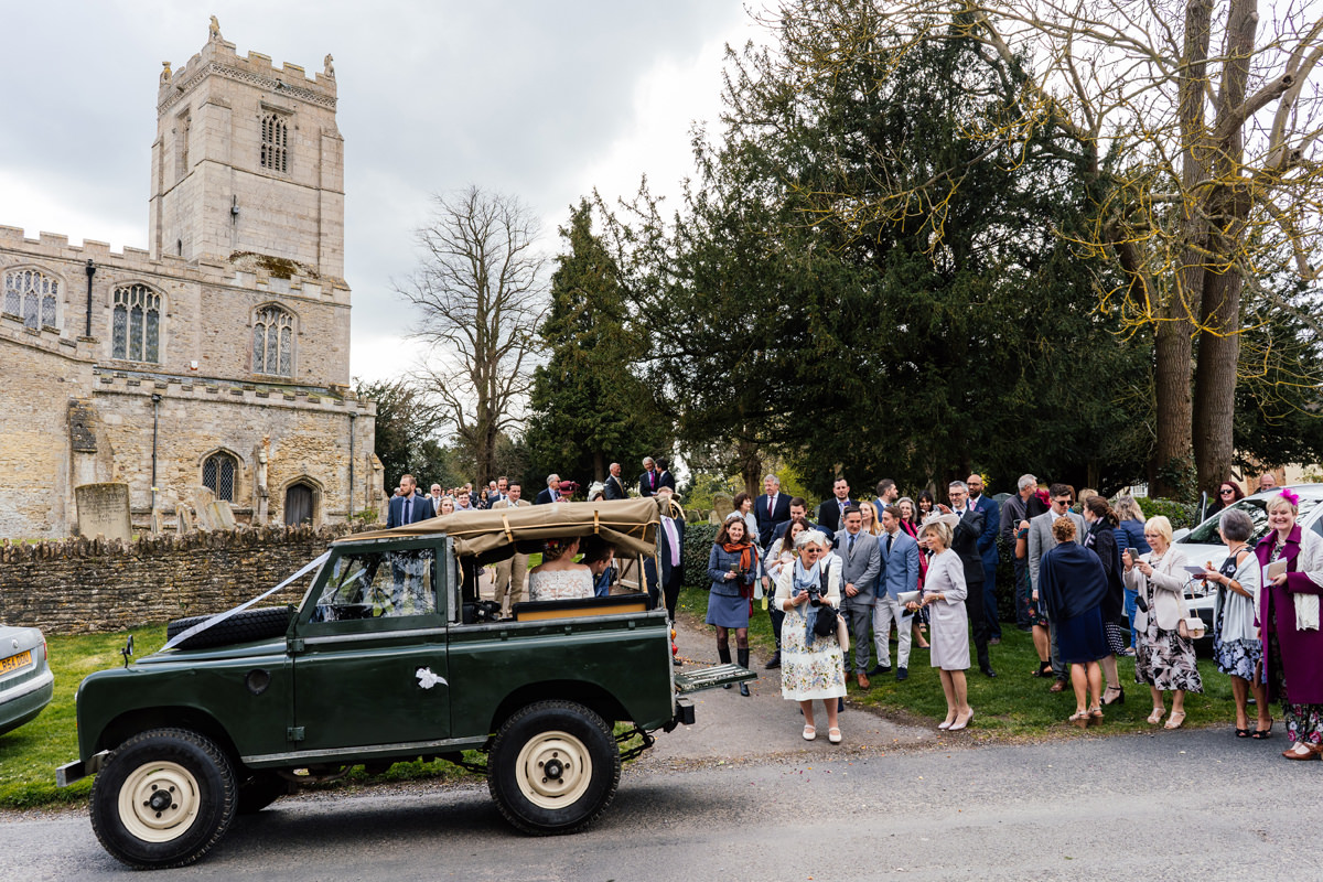 bride and groom leave the church in landcover defender