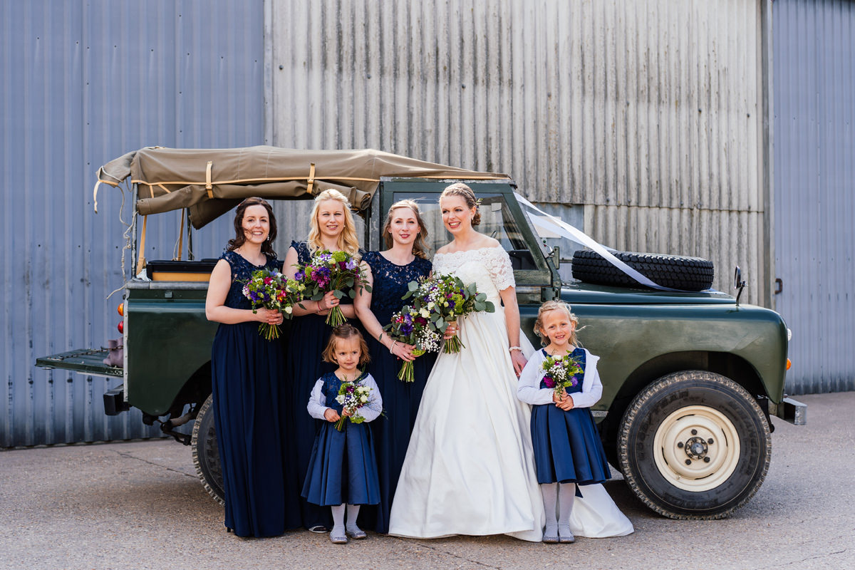 bridesmaids formal group photo with landcover defender