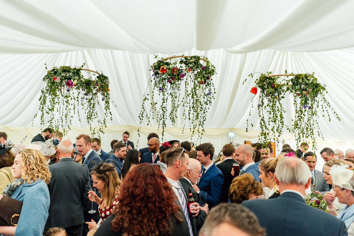 drinks reception with marquee flower arrangements