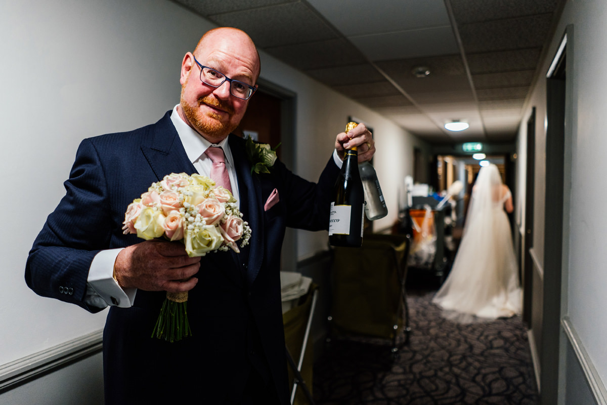 father of the bride with flowers and bottle of champagne