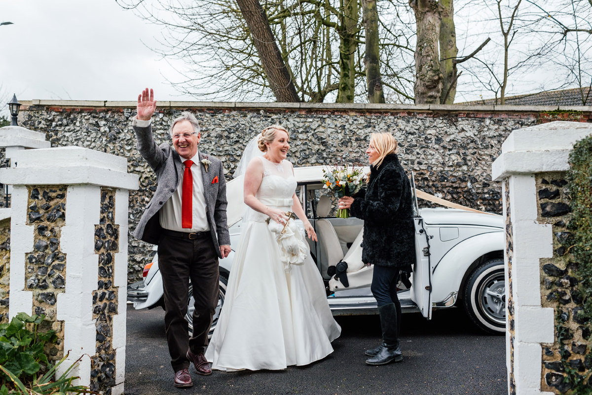 father of the bride waves as they first arrive at the church