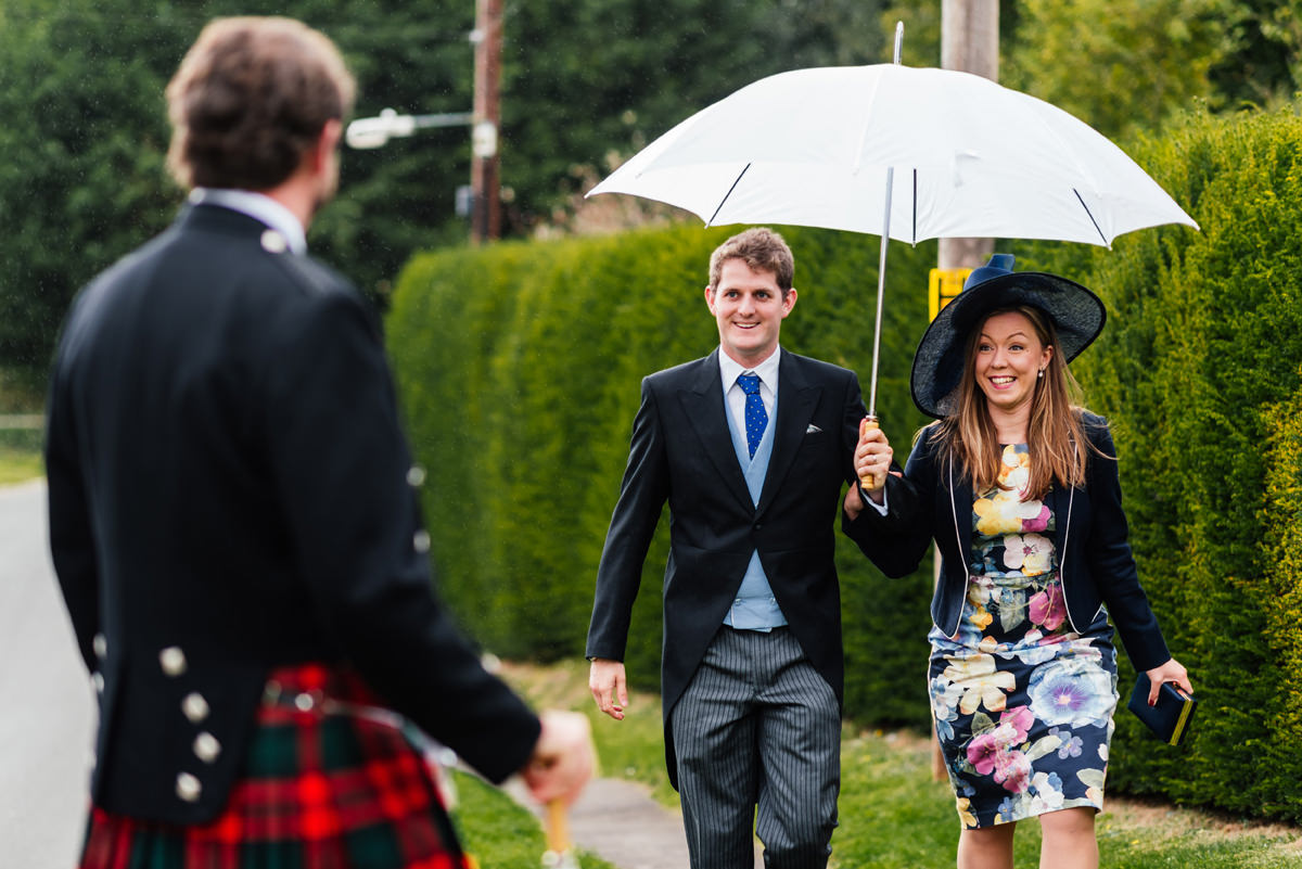 wedding guests arrive in the rain with umbrella