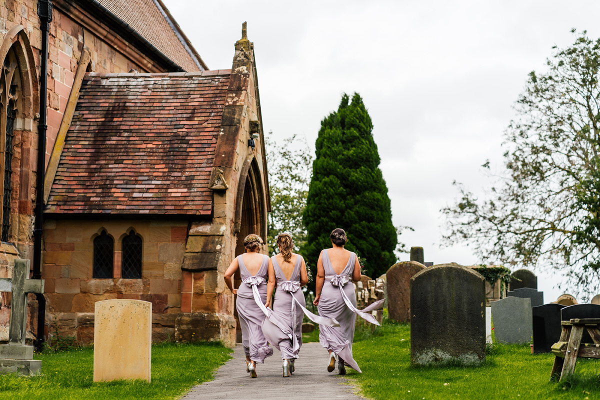 bridesmaids make their way to the church in the wind and rain