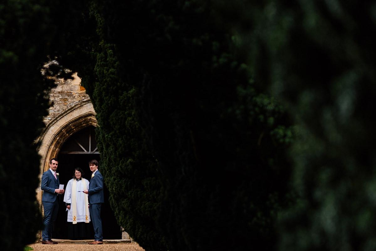 Vicar and groomsmen waiting at church entrance