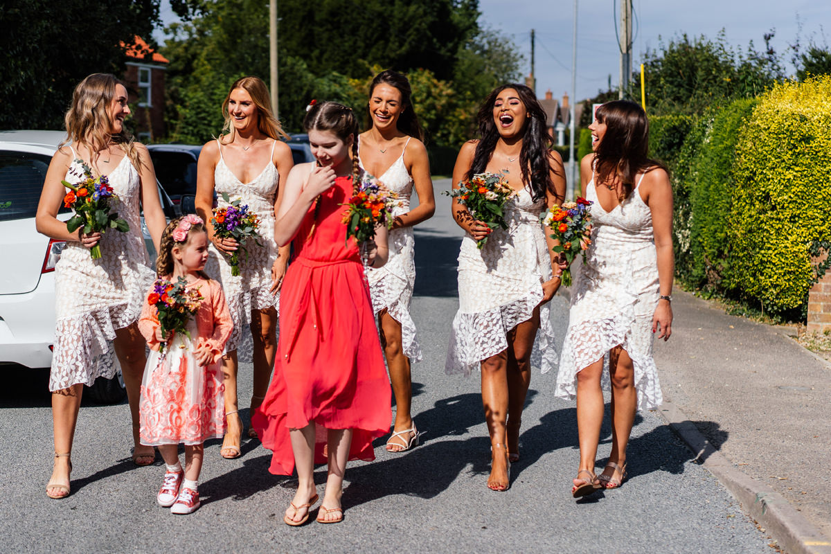bridesmaids and flower girls walk to the ceremony
