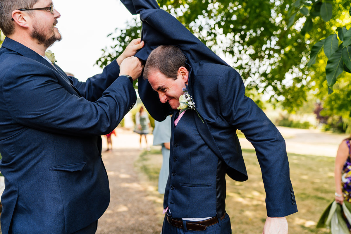 Groom struggling to get his jacket on