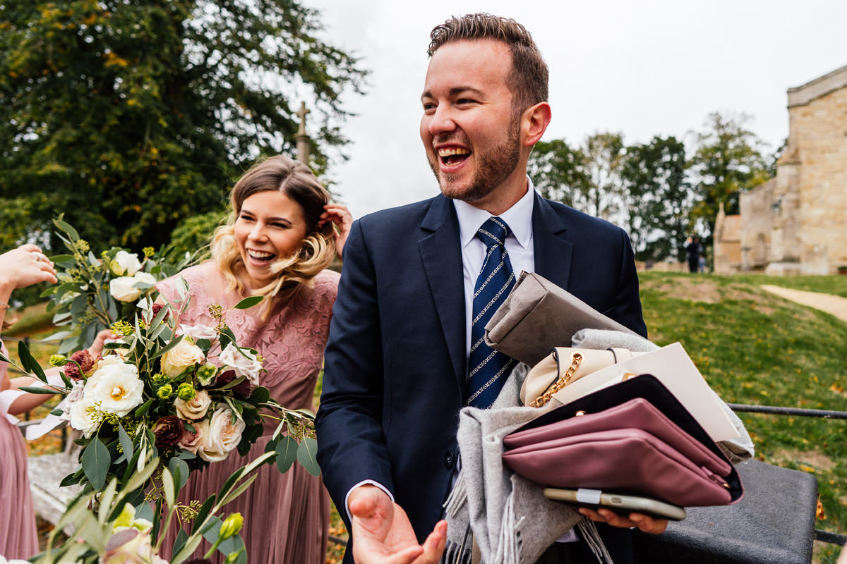 friend of the bride takes all of the bridesmaids bags for safe keeping