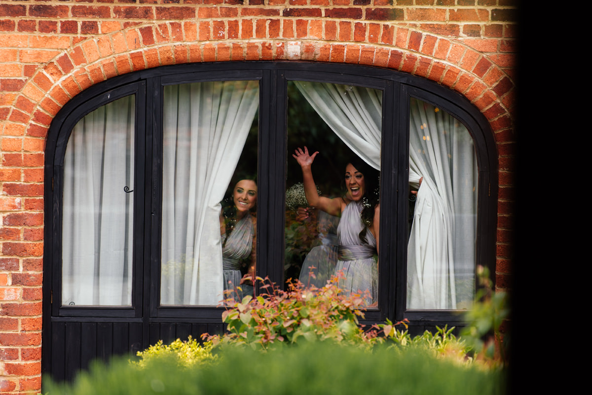 Bridesmaids wave as guests arrive at the venue