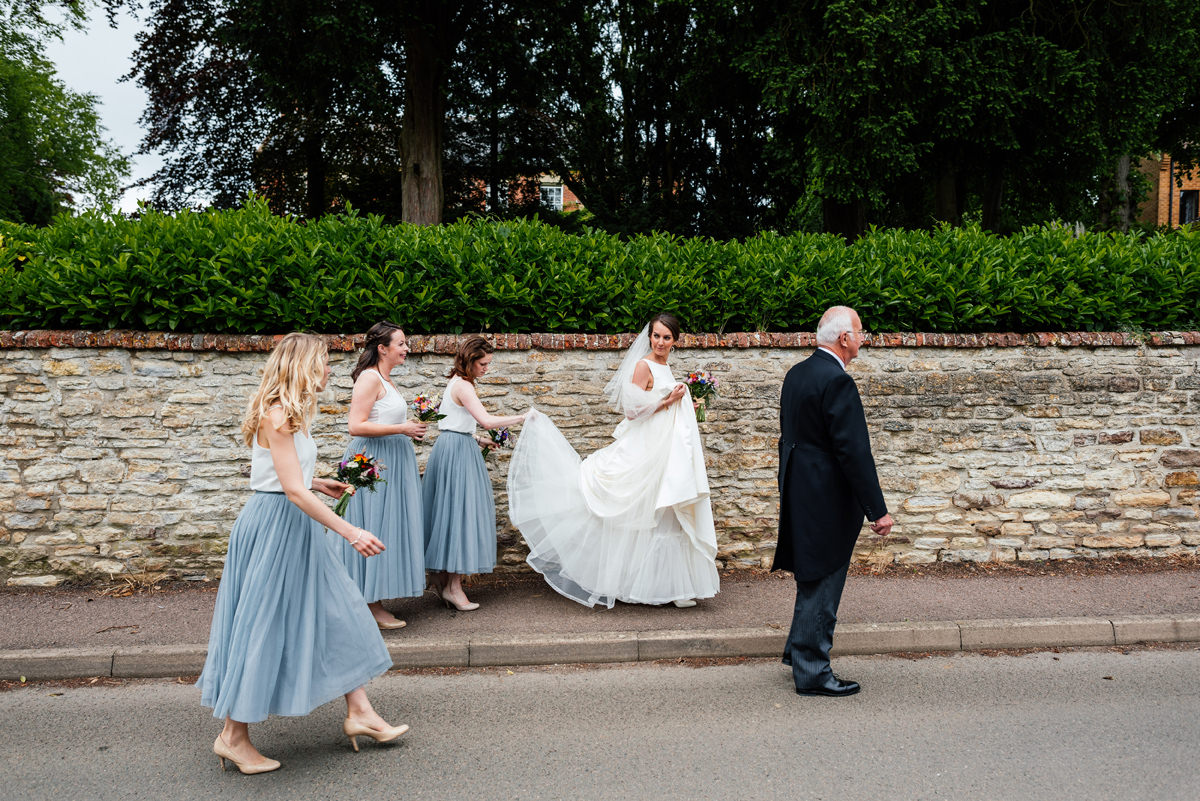 bride and bridesmaids make their way to the church