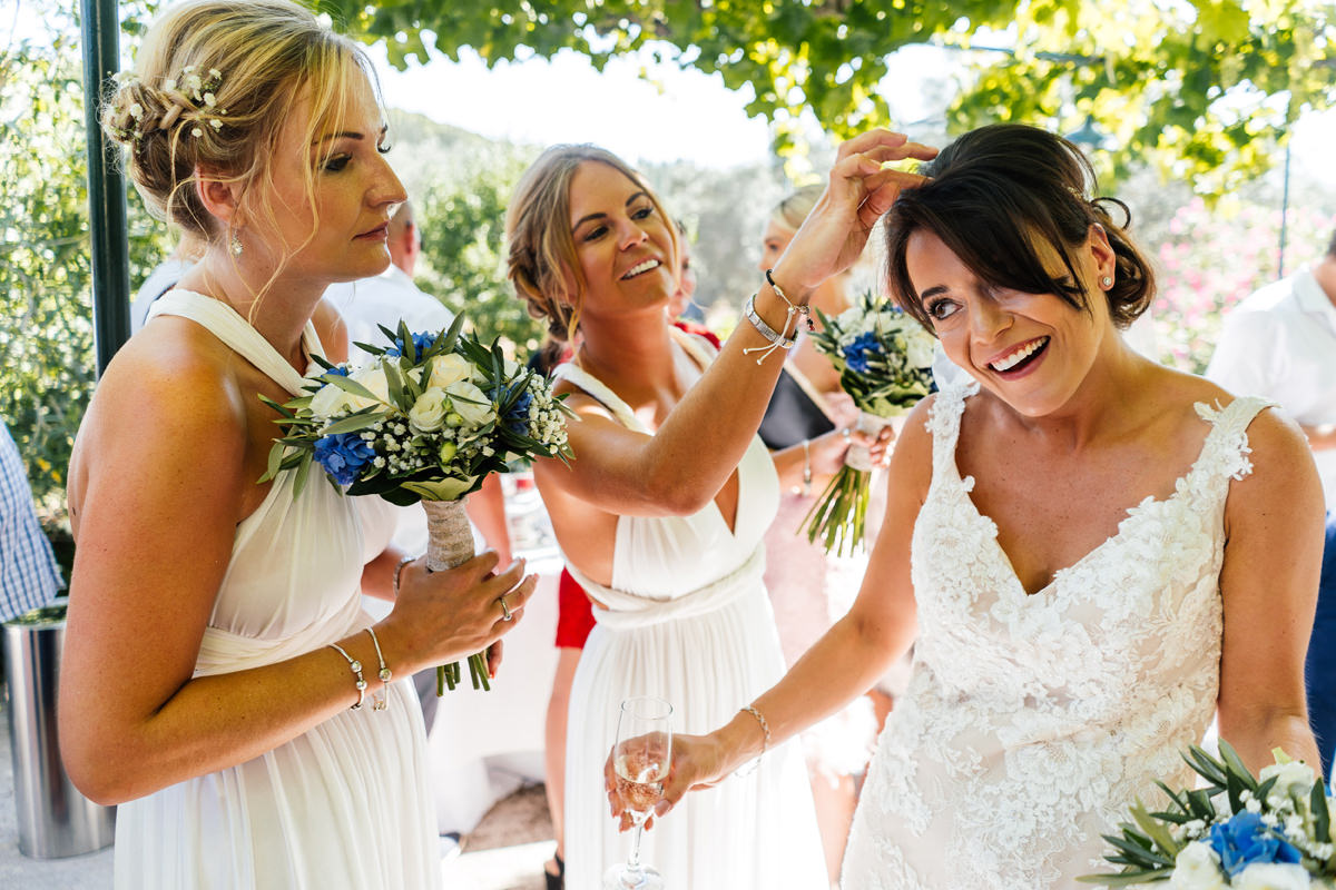bridesmaids help get the confetti out of brides hair