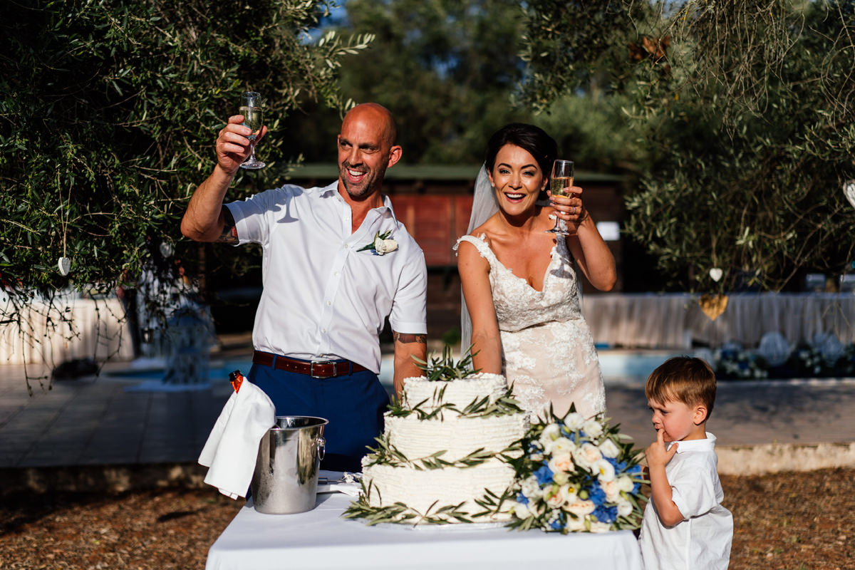 bride and groom cutting a traditional greek wedding cake