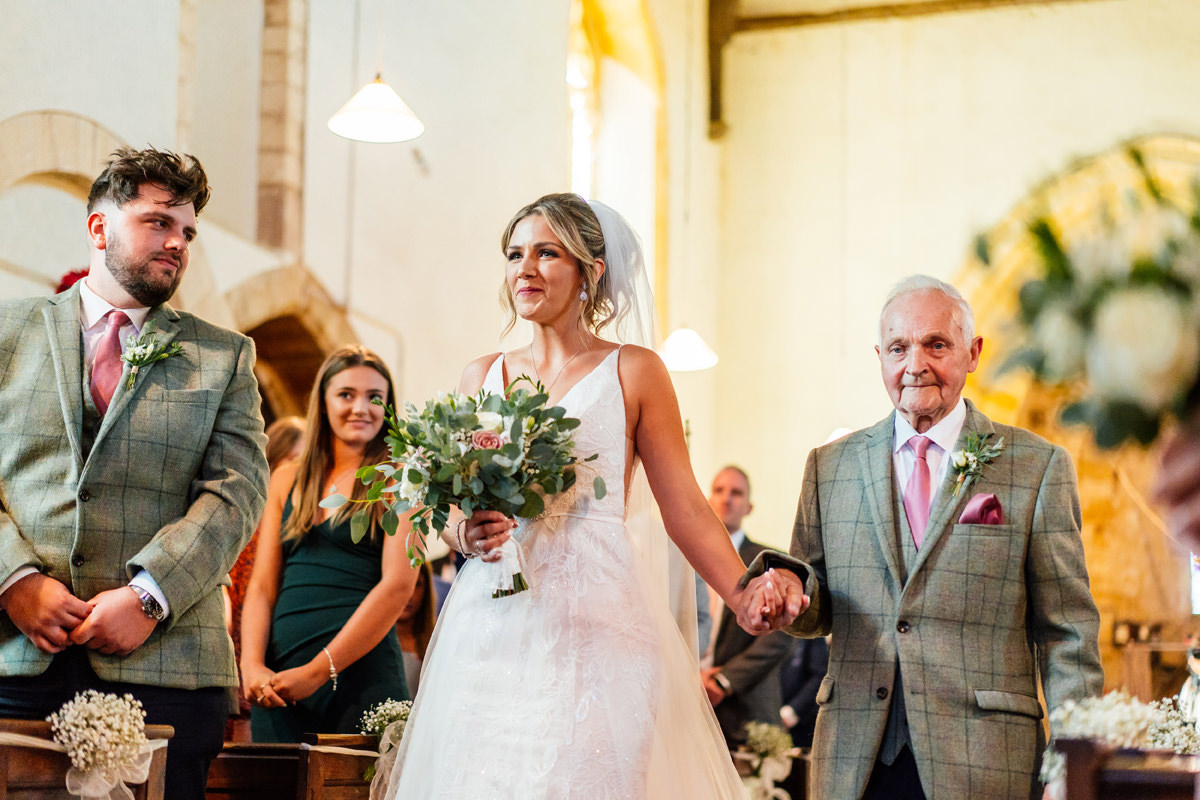 grandfather walks the bride down the church aisle