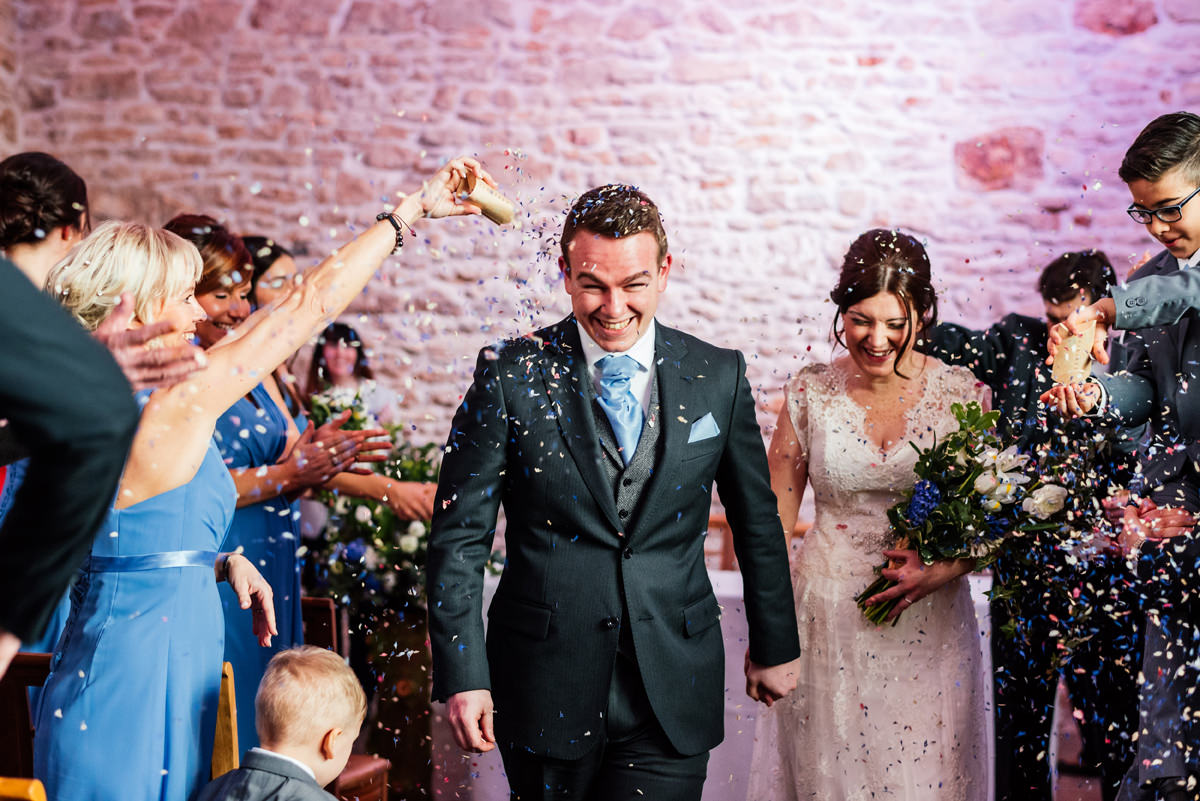 newly married couple walk the aisle showered with confetti