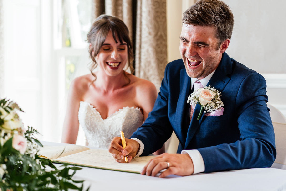 bride and groom have fun signing the marriage register
