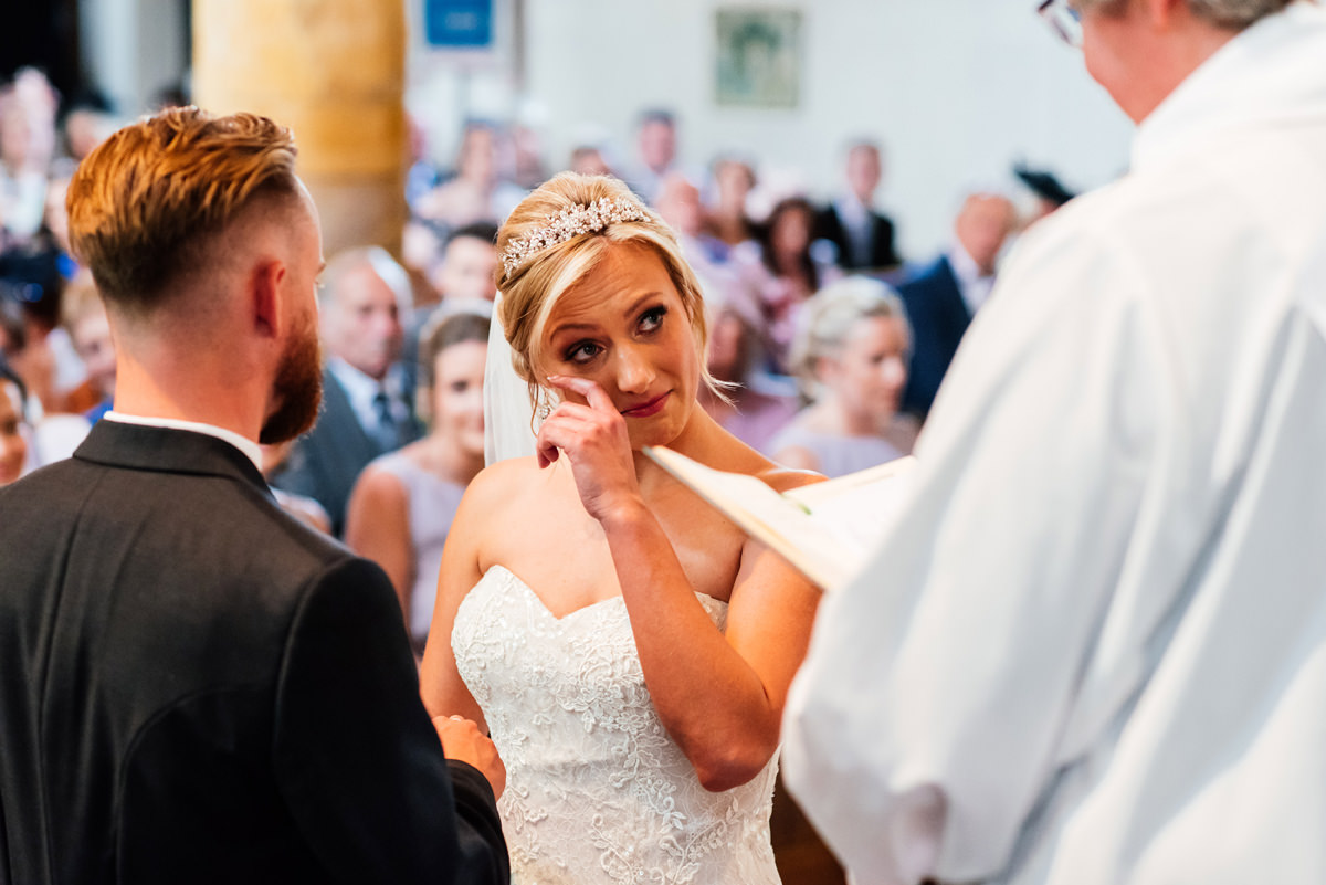 Bride wipes a tear from her eye during church ceremony
