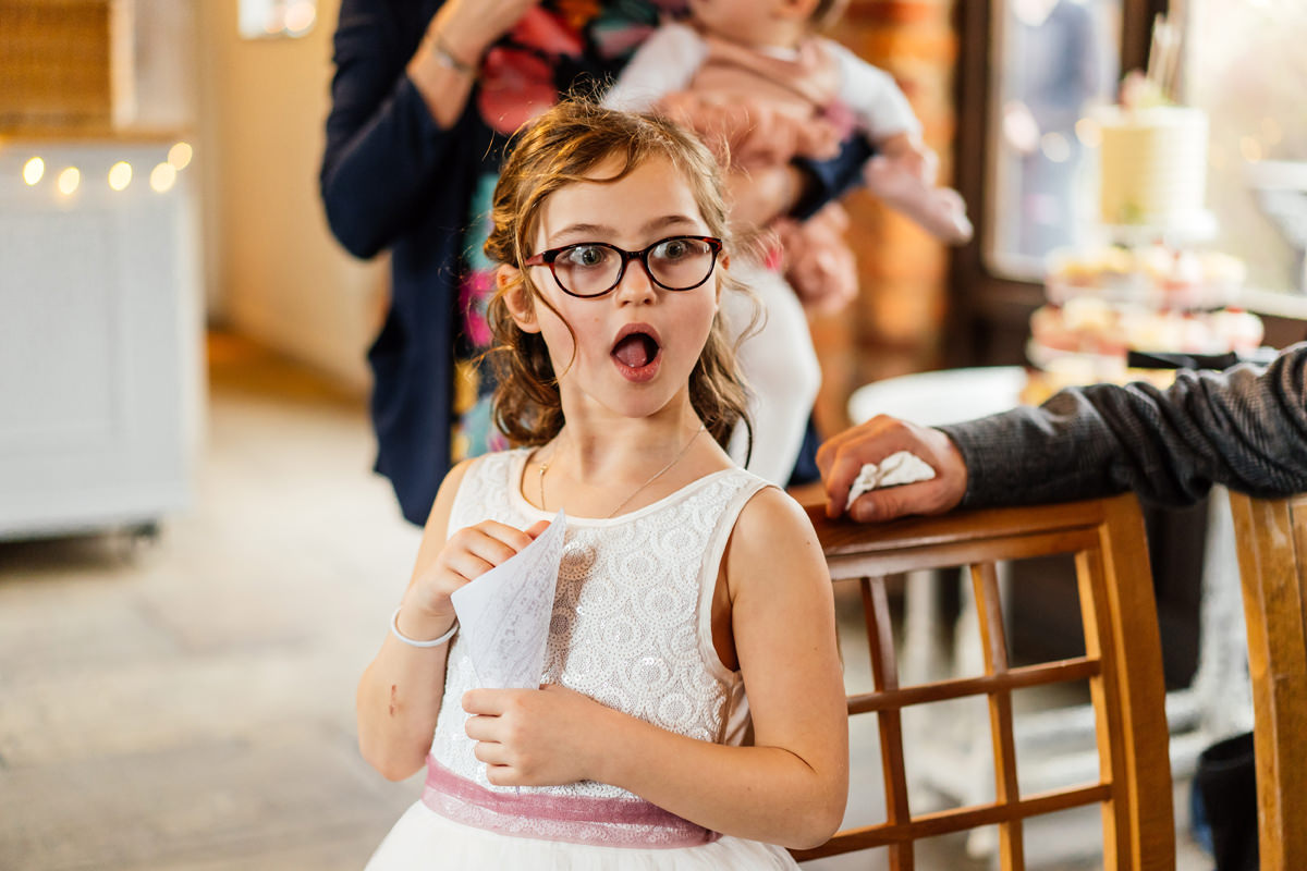 flower girl shocked face but ready to throw confetti