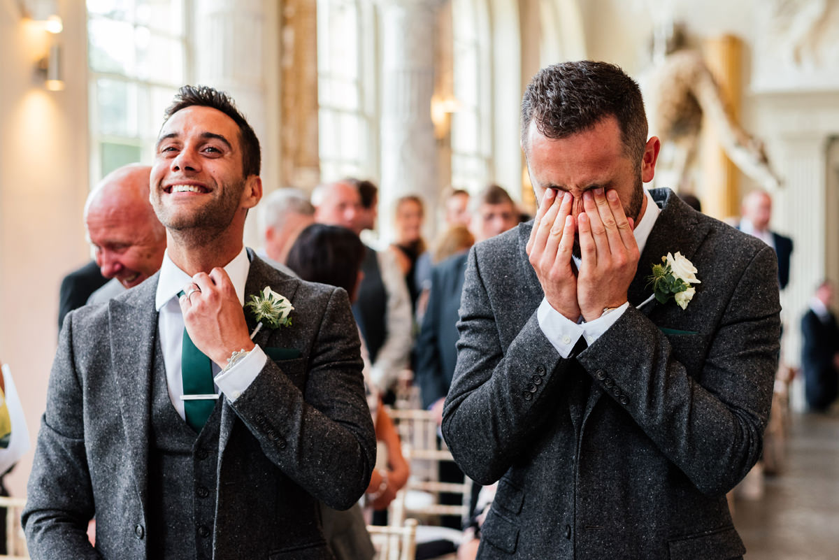 Nervous groom rubs his eyes whilst best man laughs