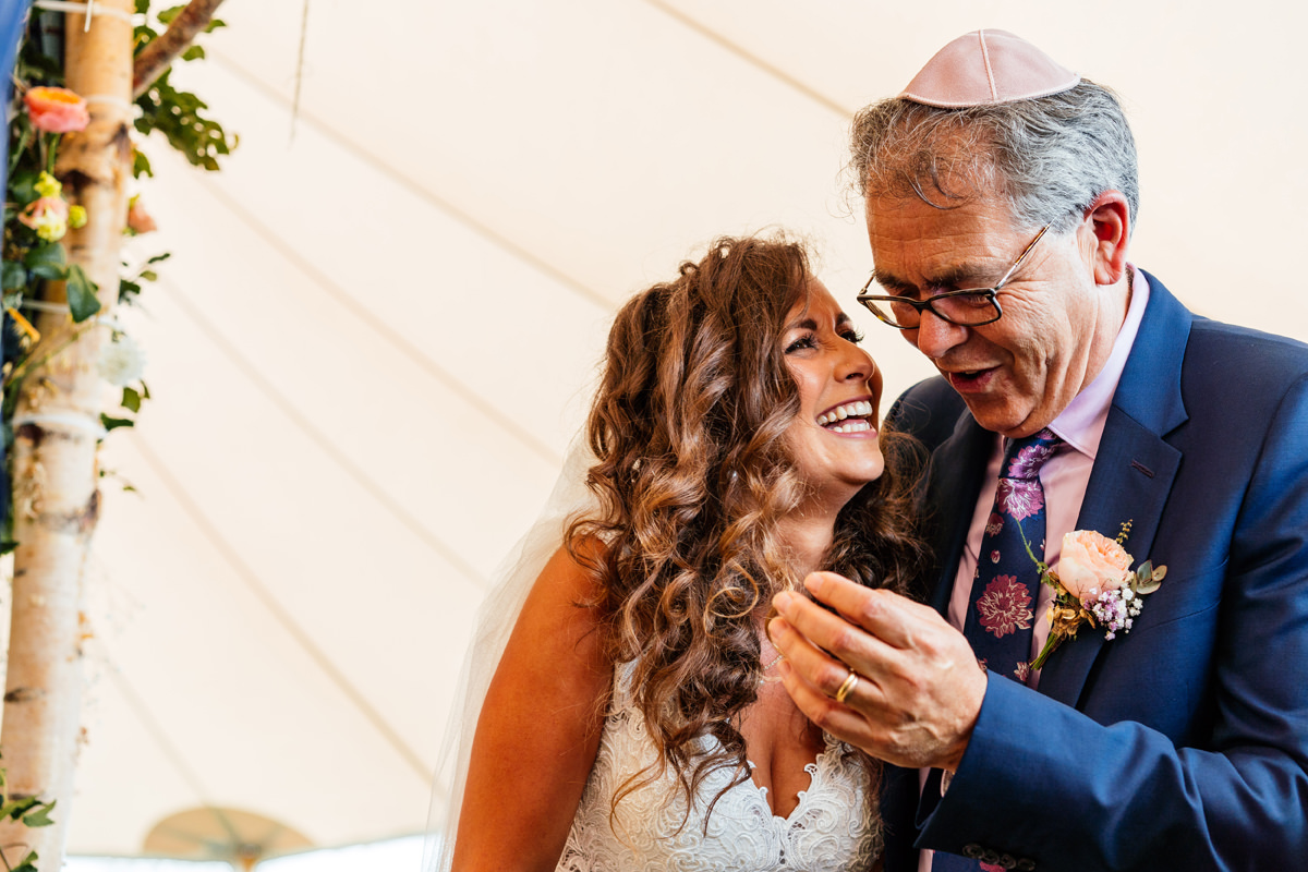 bride and father share laughter during jewish ceremony