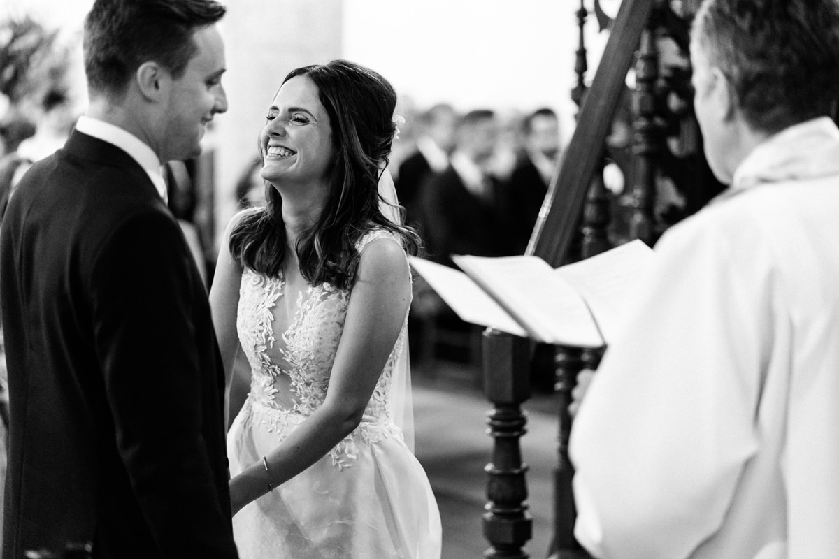 bride laughing with groom in church