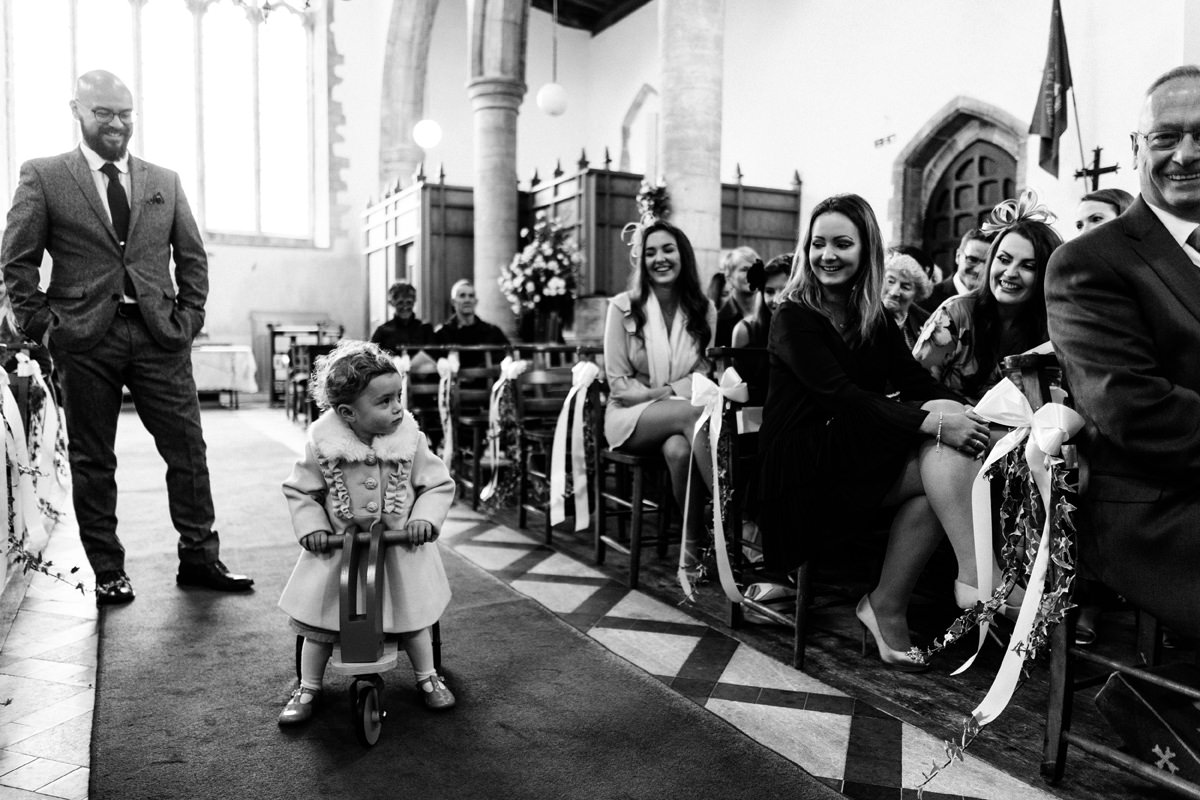 child on a bike in the aisle of church during marriage ceremony