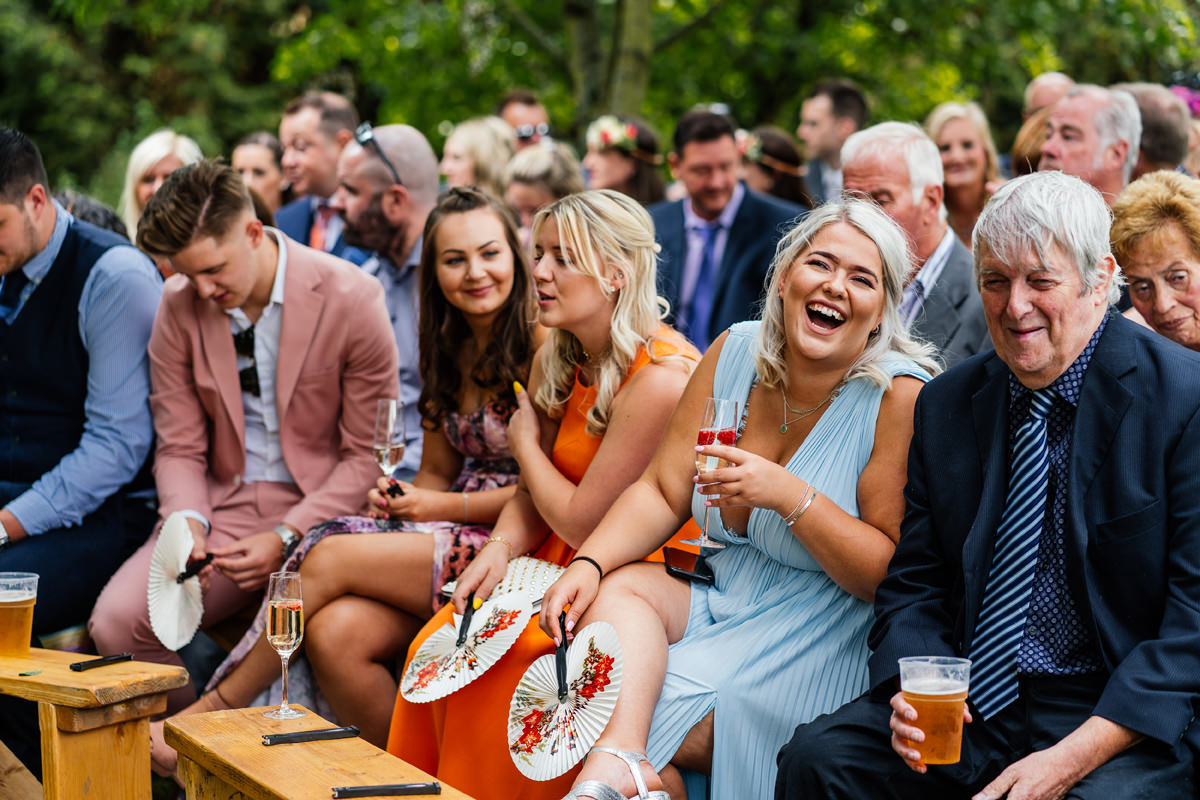 wedding guests laughing as they wait for the ceremony to start at an outside ceremony
