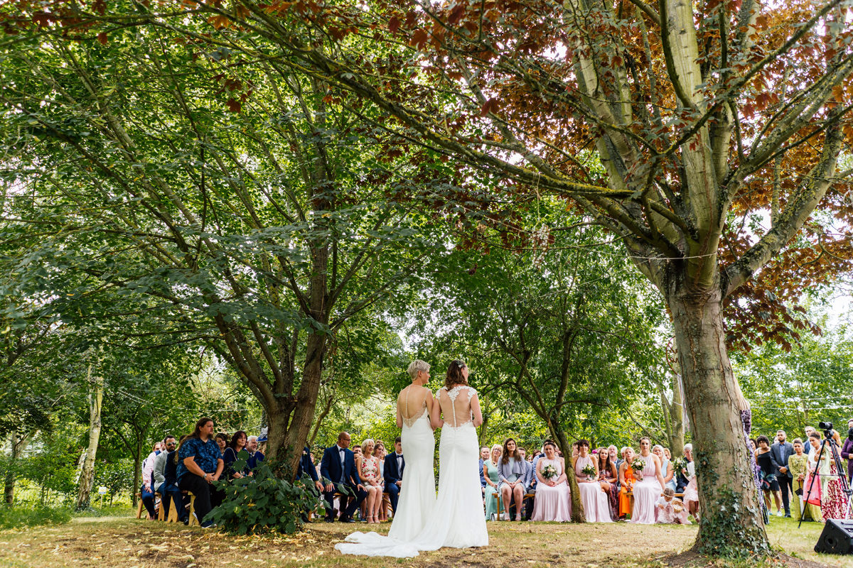 two brides hold hands during outdoor wedding ceremony