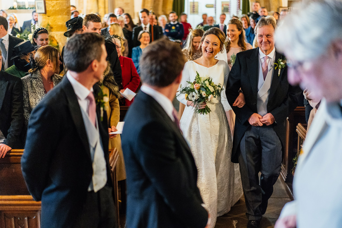 bride arrives walks with father down aisle of church