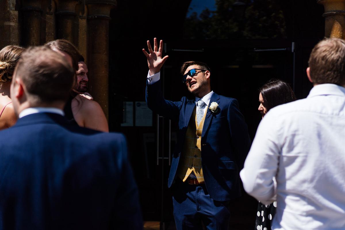 groomsman greeting wedding guests at the church