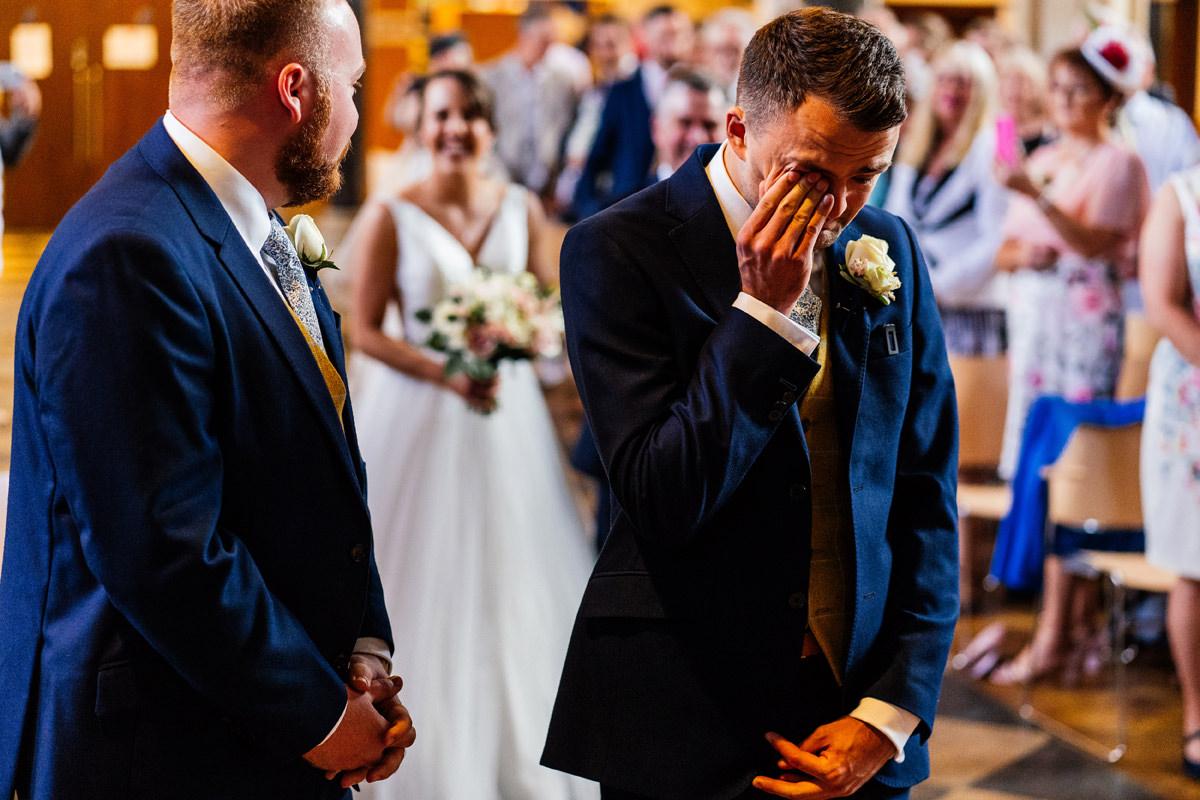 groom has a wipe of the eye as bride walks up the aisle
