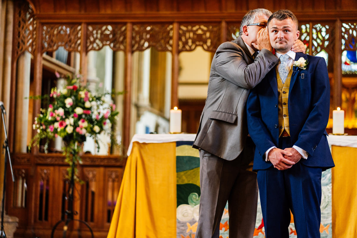 Vicar whispers to the groom during a reading