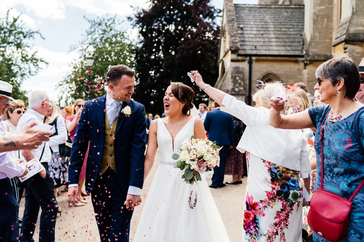 wedding guests throw confetti at the bride and groom
