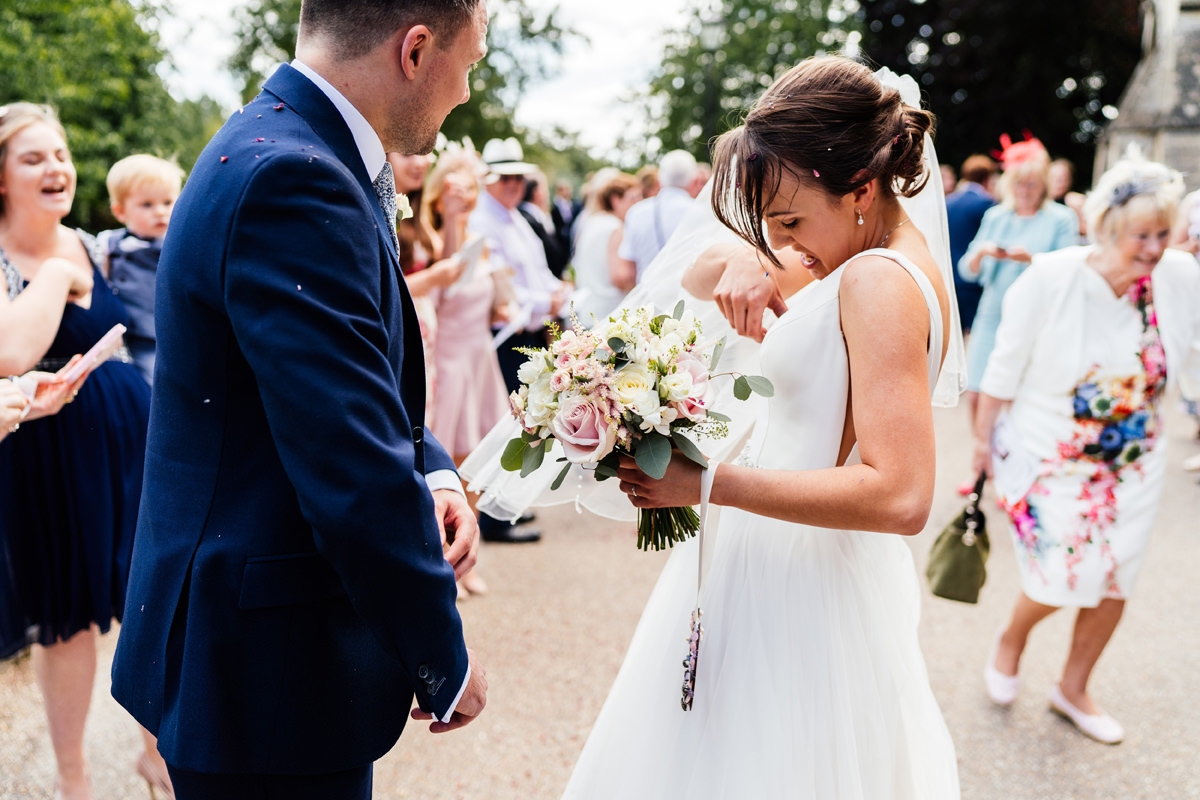 bride tries to remove the confetti from her dress