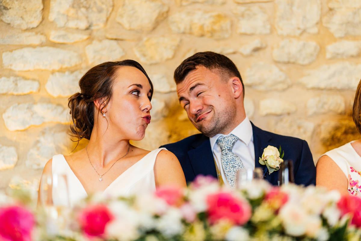 bride and groom pulling silly faces at each other