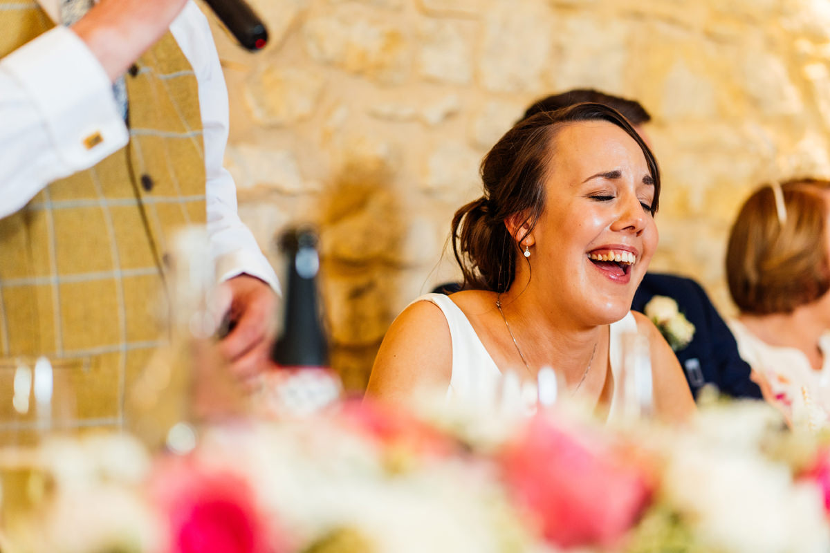 bride laughing during her dads speech