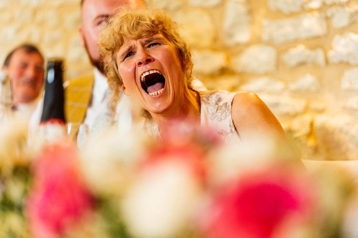mother of the groom laughing during the speeches