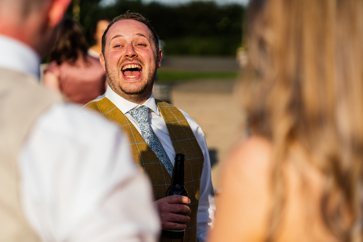 Groomsman laughing during evening drinks reception