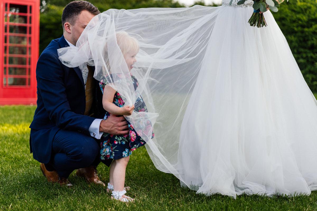 child under the bride's dress