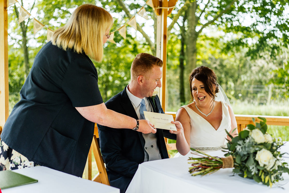couple being handed their marriage certificates