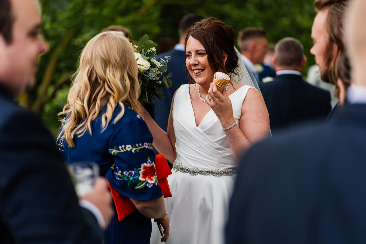 bride chatting with guests and enjoying an ice cream during the drinks reception